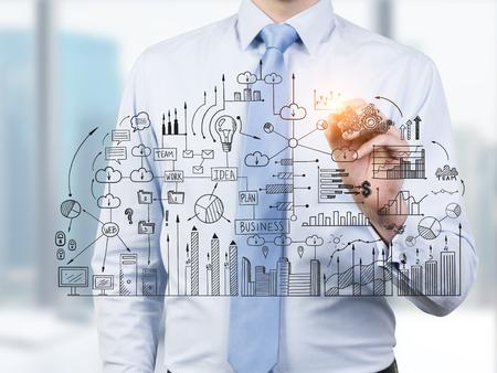 Gros plan d'un homme d'affaires vêtu d'une chemise bleue et une cravate et de dessiner un plan d'affaires sur un panneau de verre dans son bureau. Banque d'images - 75563459