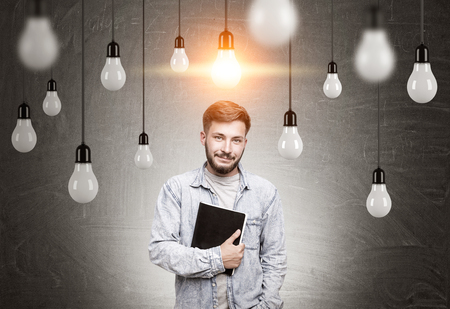 bearded wires: Portrait of a bearded young man wearing a jeans shirt and holding a black notebook while standing in a black room with many light bulbs hanging on their wires. Toned image. Stock Photo