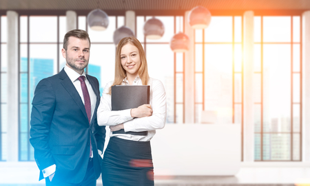 Two business partners are standing together near a white reception counter in an office lobby. Toned image