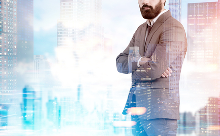 Unrecognizable bearded businessman in is standing with crossed arms against a blue city panorama. Toned image, mock up, double exposure