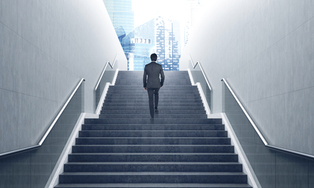 Rear view of a businessman ascending a staircase in a city. Cityscape is in the background. Toned image, film effect. 3d rendering