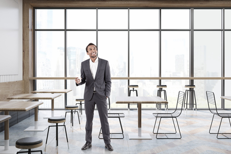 dinning: African American man in a cafe with panoramic windows, square wooden tables, transparent chairs and bar stools. 3d rendering. Stock Photo