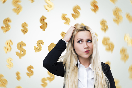 earn money: Portrait of a confused blond businesswoman scratching her head while staning near a gray wall with dollar signs