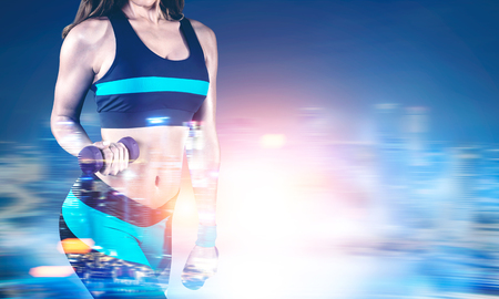 Close up of a young woman wearing black and blue sportswear and holding dumbbells standing against a blurred night city background. Mock up, toned image