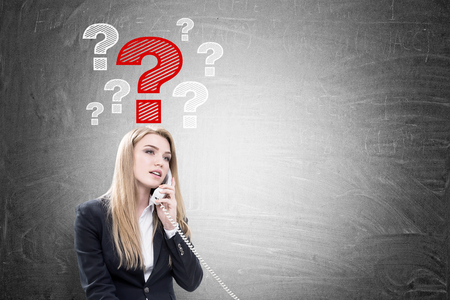 scratches: Portrait of a blond businesswoman talking on the phone while sitting near a blackboard with question marks drawn on it. Mock up Stock Photo