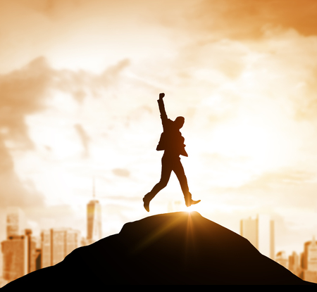 Silhouette of a businessman jumping on a hill. There is an orange cityscape in the background. Mock up