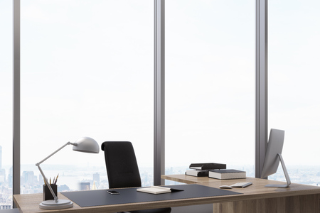 Close up of a CEO table with a computer standing on it and a panoramic window behind it. 3d rendering
