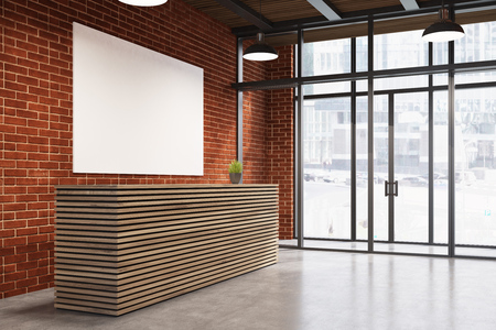 Side view of a wooden reception counter standing near a brick wall with a poster hanging on it and and a glass door in the background. 3d rendering, mock up Stock Photo