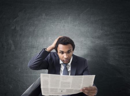 空白黒板近く新聞を肘掛け椅子に座っていると信じられない思いでそれで見て驚いてアフリカ系アメリカ人実業家の肖像画。モックアップします。