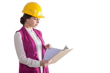 architect: Isolated portrait of a woman wearing a yellow hardhat and a pink west and holding a clipboard with documents. Stock Photo