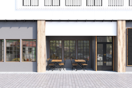 cappucino: Cafe exterior with gray walls and two wooden tables with chairs standing near a door. 3d rendering Stock Photo