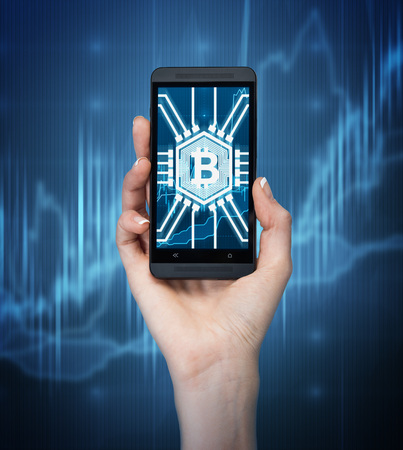 bitcoin network: Close up of a woman s hand holding a smartphone with a bitcoin symbol on its screen. Dark blue background with graphs.