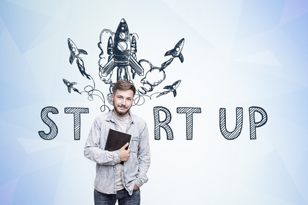 accelerated: Portrait of a young bearded man holding a black book and standing near a blue wall with a start up sketch