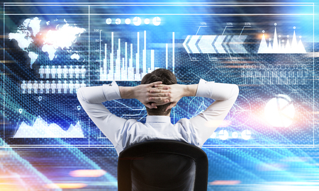 Rear view of a businessman sitting with his arms behind the head and looking at graphs. Elements of this image furnished by NASA. Toned image Stock Photo