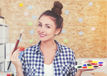 Portrait of a cheerful woman painter in a blue checkered shirt holding a palette and a paintbrush. Toned image Stock Photo