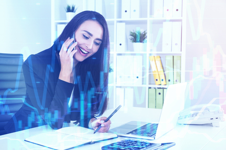 Portrait of a cheerful businesswoman talking with a client on a phone in her office and smiling. Graphs in the foreground. Toned image. Stock Photo