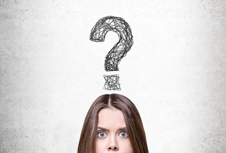 answer: Close up of a confused young woman with brown hair standing near a concrete wall with a large question mark above her head