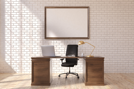 Front view of a CEO table with a laptop standing on it. There is a framed horizontal poster on a brick wall behind it. 3d rendering, mock up Stock Photo