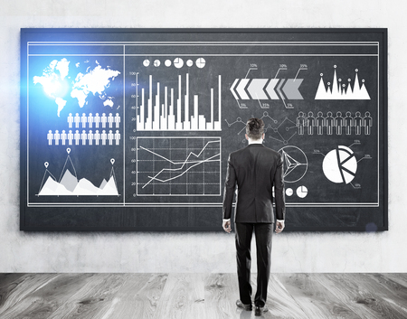 Rear view of a businessman looking at graphs drawn on a blackboard. Elements of this image furnished by NASA. Toned image