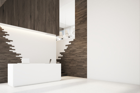 Side view of a dark wooden wall with a reception counter standing near it. There are two laptops on it and a staircase in the niche. 3d rendering, mock up