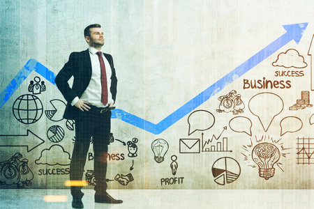 Confident bearded businessman is standing with hands on the waist near a concrete wall with business plan icons and a blue graph. Mock up, toned image