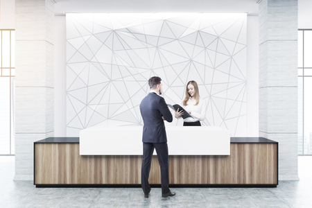 El hombre de negocios está hablando con un recepcionista en un contador de la recepción de madera y blanco de una construcción original que se coloca cerca de una pared blanca con un modelo geométrico en ella. Representación 3D