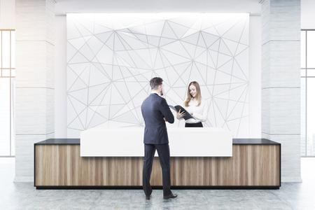 L'uomo d'affari sta parlando con un assistente alla reception di un banco di ricevimento in legno e bianco di una costruzione originale in piedi vicino a una parete bianca con un motivo geometrico su di esso. Rendering 3D