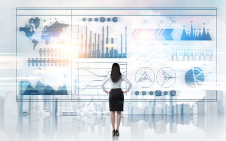 Rear view of a businesswoman standing with her arms on the waist and looking at graphs in sky. Elements of this image furnished by NASA. Toned image