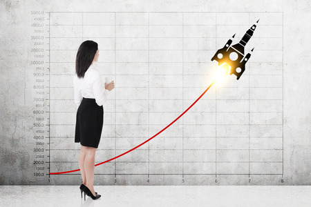 Side view of a businesswoman holding a paper cup of coffee and looking at a red growing rocket graph on a concrete wall Stock Photo