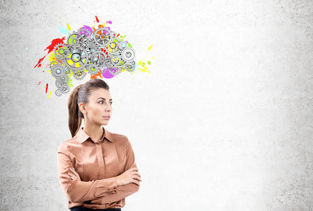 thinking machines: Portrait of a young woman wearing a brown blouse and standing with crossed arms near a concrete wall with a colored brain shape and gears on top of it. Mock up Stock Photo