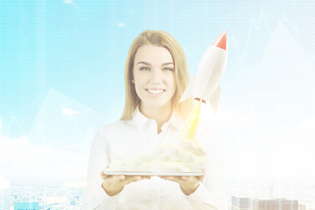 Portrait of a blond businesswoman holding a tablet with a small rocket taking off from it. Cityscape in the background. 3d rendering, toned image