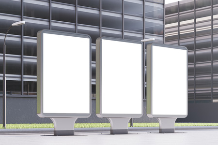 lightbox: Side view of three glowing empty billboards standing in a street near an office building. 3d rendering, mock up
