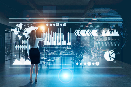 Rear view of a blond businesswoman interacting with graphs holograms in a futuristic setting. Elements of this image furnished by NASA. Toned image, double exposure Stock Photo