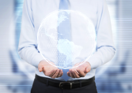 businessman carrying a globe: Close up of a businessman wearing a blue tie and standing in his office holding an Earth hologram with both hands. Elements of this image furnished by NASA