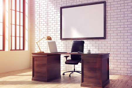 Side view of a CEO table with a laptop standing on it. There is a framed horizontal poster on a brick wall behind it. 3d rendering, mock up, toned image