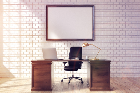 Front view of a CEO table with a laptop standing on it. There is a framed horizontal poster on a brick wall behind it. 3d rendering, mock up, toned image