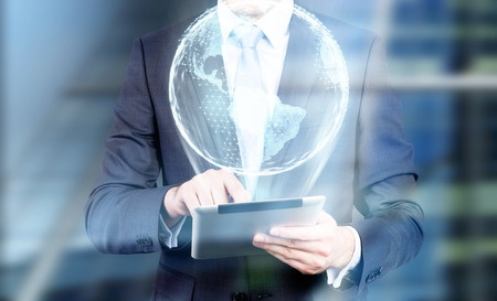 Close up of a businessman wearing a blue tie and holding a tablet with an Earth hologram emerging from it. Elements of this image furnished by NASA Stock Photo