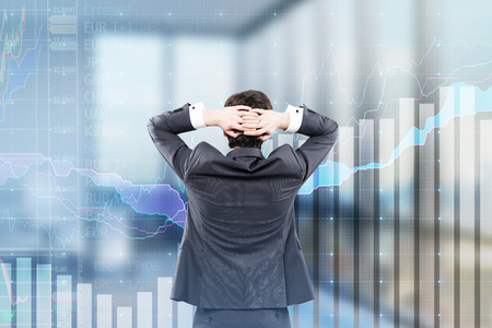 Rear view of a businessman standing with hands behind the head and looking at transparent graphs in his blurred office. Stock Photo