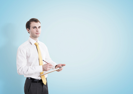 clothes organizer: Portrait of a young businessman wearing a white shirt and a yellow tie, holding a clipboard and a pencil and standing near a blue wall. Mock up