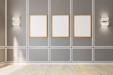 Three framed vertical posters are hanging on a gray wall in an empty room with wooden floor and modern wall lamps. 3d rendering, mock up Stock Photo