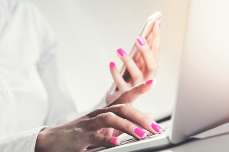 Close up of businesswoman s hands with pink nail polish holding a smartphone and typing with the second hand. Toned image