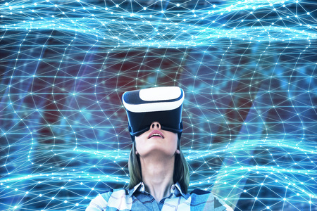 Portrait of a young woman wearing a shirt and VR glasses looking upwards standing against abstract blue background Stock Photo