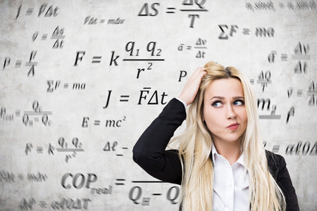 formulae: Close up of a young blond woman scratching her head near a concrete wall with formulae written on it. Concept of lack of women in science Stock Photo