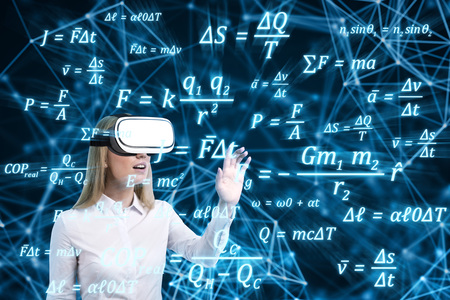 formulae: Blond woman in vr glasses is mesmerised by formulae she is seeing in front of her. Concept of the future is now.