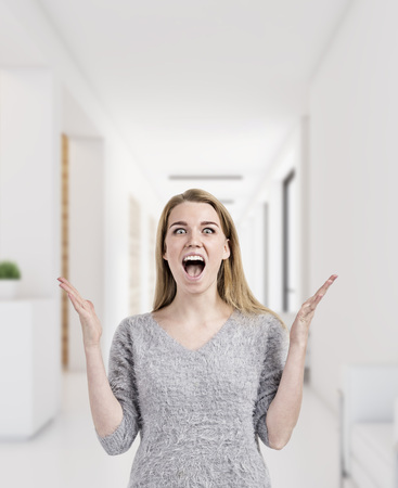 Portrait of a blond woman in a gray sweater screaming with joy and absolutely happy about her career choice in a white office. 3d rendering mock up