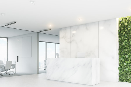 Corner of a white reception desk with two laptops standing on it in front of a marble office wall. There is a grass wall seen through a wall opening. 3d rendering, mock up