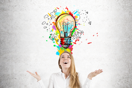 Close up of a happy blond businesswoman standing with an open mouth near a concrete wall with a colorful light bulb above her head