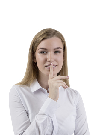 Isolated portrait of a blond businesswoman wearing a white shirt and making a hush sign. Concept of conspiracy and keeping a secret Stock Photo