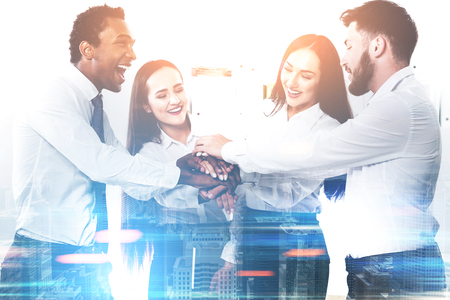 teaming up: Members of a diverse business team are standing in a circle with their hands together teaming up. They are having fun and being successful. Toned image film effect