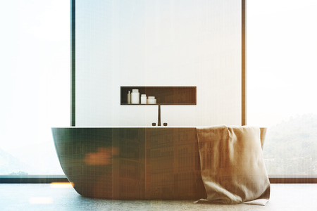 Close up of a white modern bathroom interior with a wooden tub standing near a window, a large towel hanging on its side and a shelf with cleaning products in the wall. 3d rendering, mock up, toned image Stock Photo
